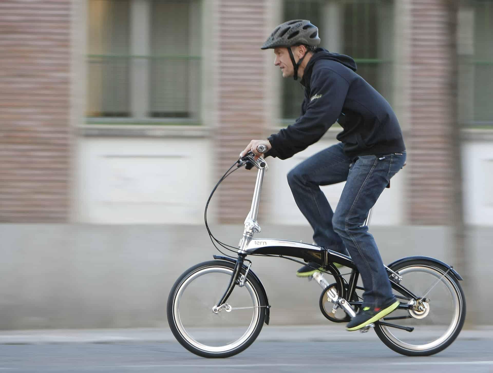 Imagem mostra um senhor pedalando uma bicicleta dobrável em uma rua vazia.