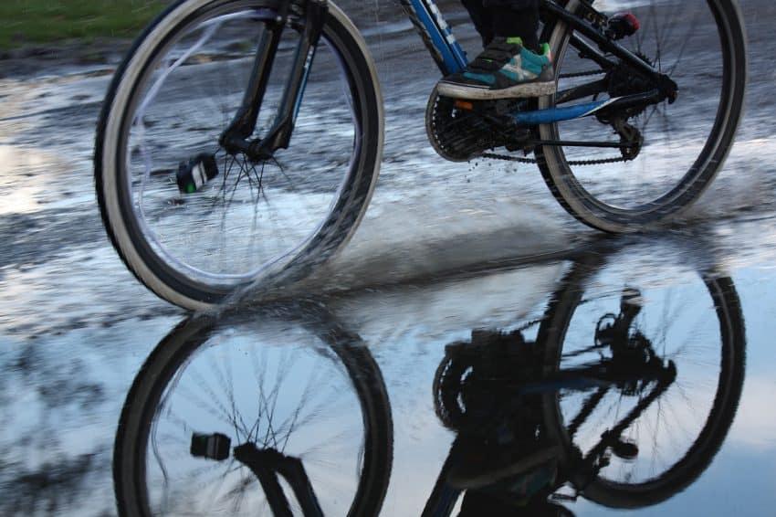 Imagem mostra rodas de bicicleta em close passando por um chão molhado.