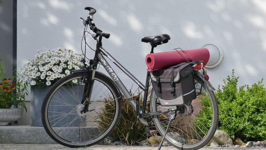 Imagem mostra um tapete de yoga no bagageiro de uma bicicleta.