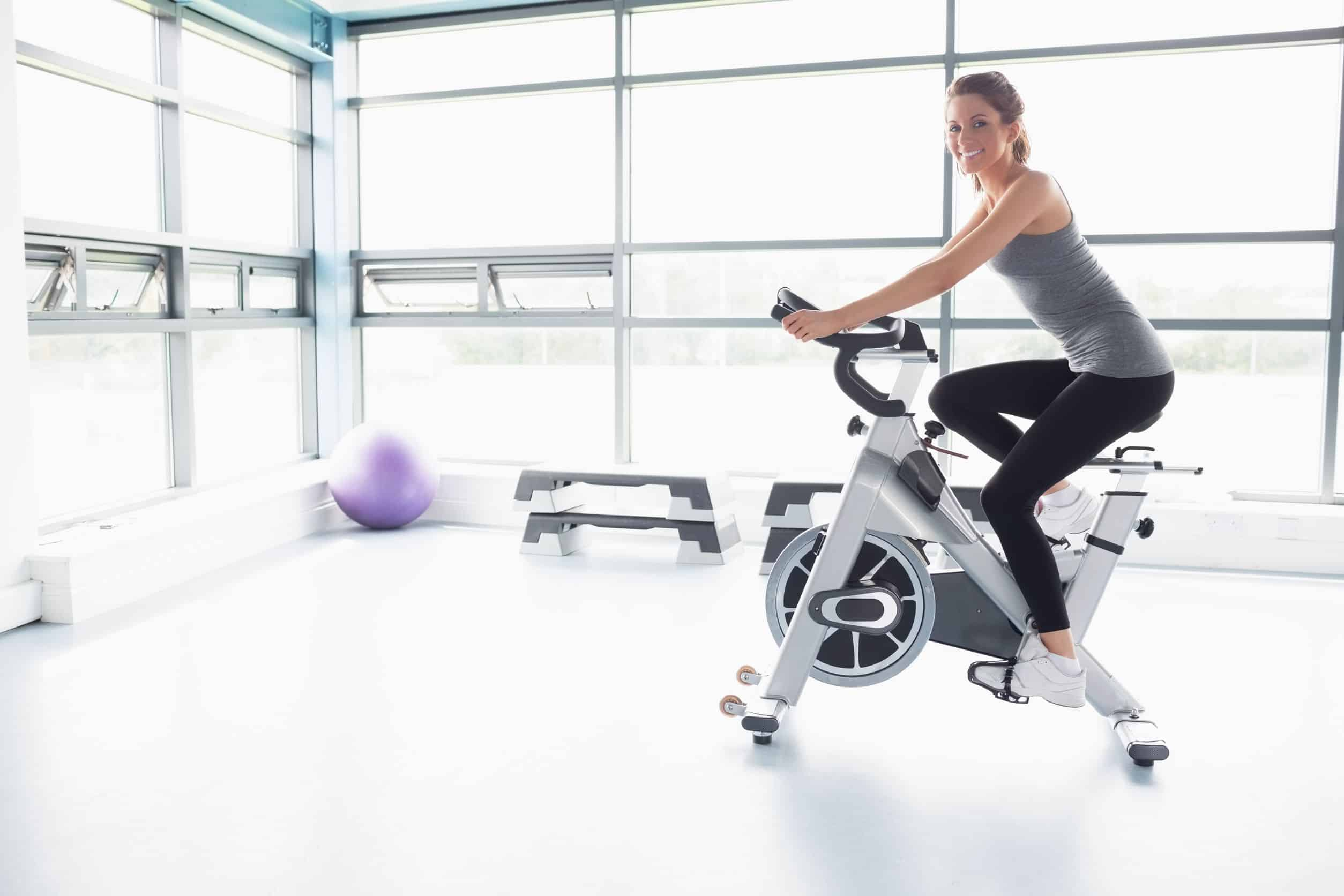 Imagem mostra mulher em uma bicicleta ergométrica em uma sala de exercícios branca.