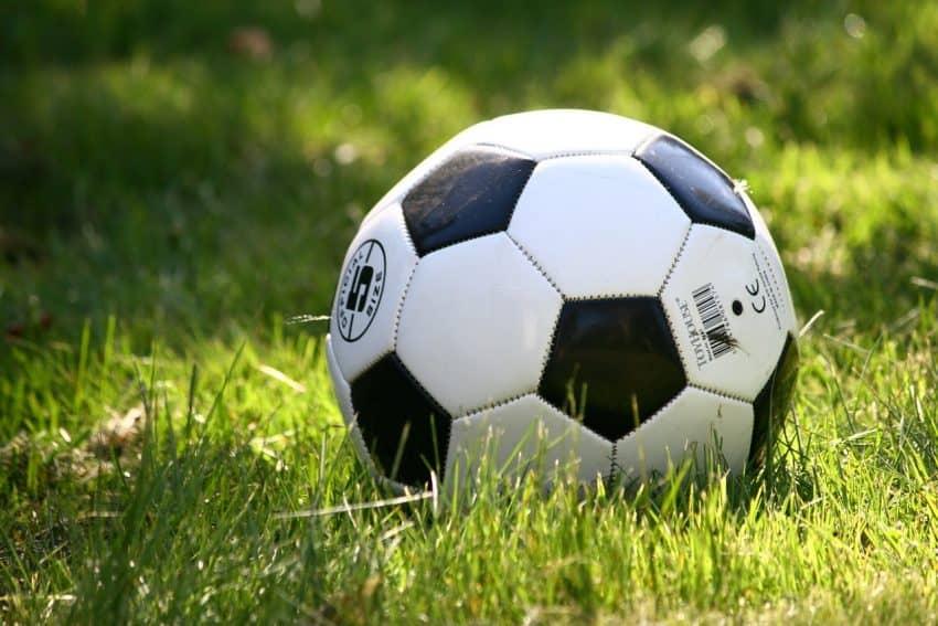 Imagem mostra uma bola de futebol em destaque em meio a um gramado.