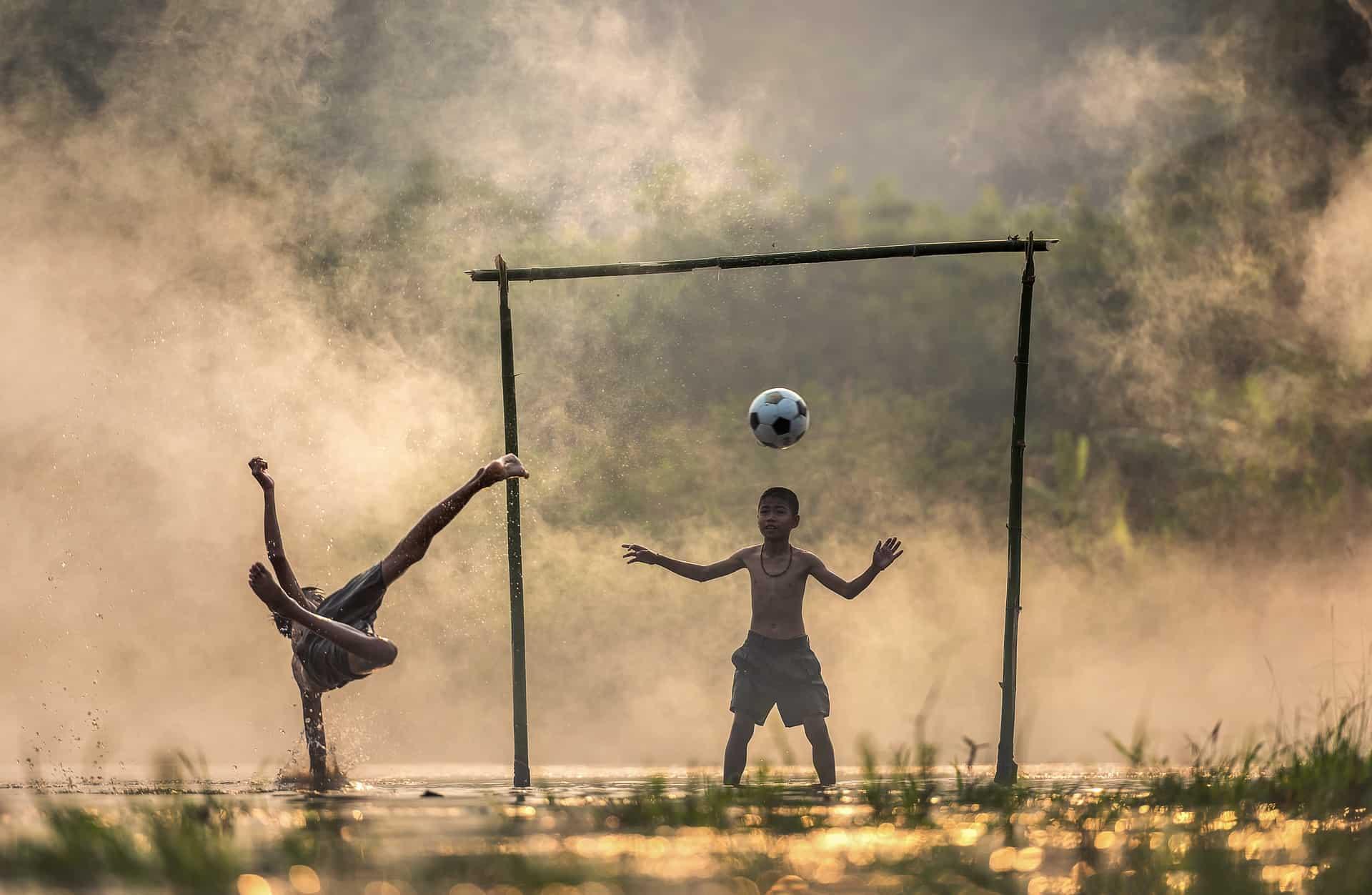 Imagem mostra um garoto chutando uma bola, de voleio, enquanto outro defende uma trave feita com pedaços de madeira. O campo é improvisado em uma paisagem com grama e água.