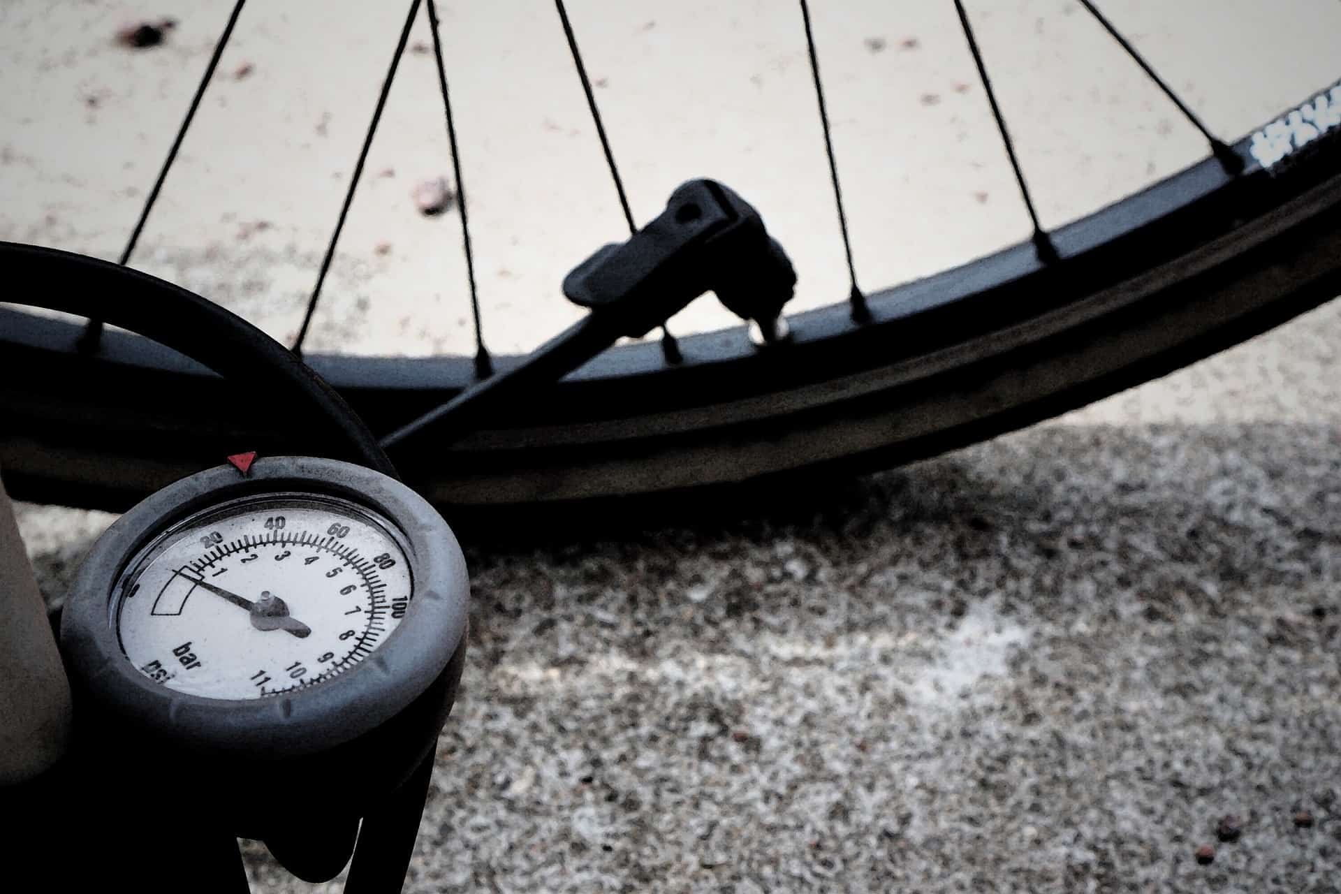 Imagem mostra manômetro em primeiro plano, ligado por uma mangueira à um bico, inserido num pneu de bicicleta em, segundo plano.