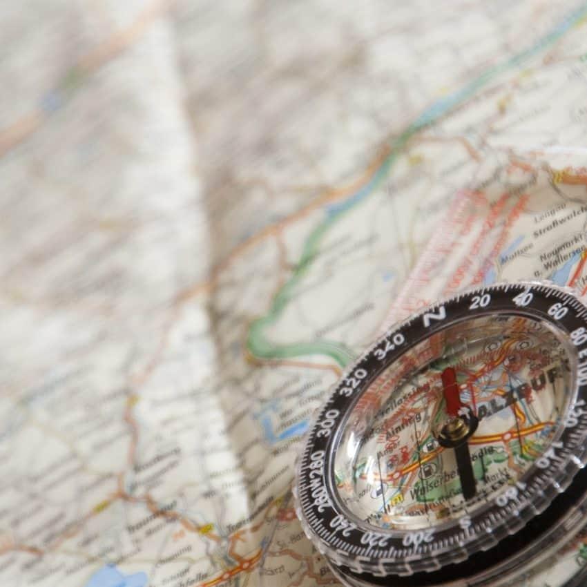 Imagem mostra bússola em disco plástico transparente apoiada em cima de um mapa de uma cidade.