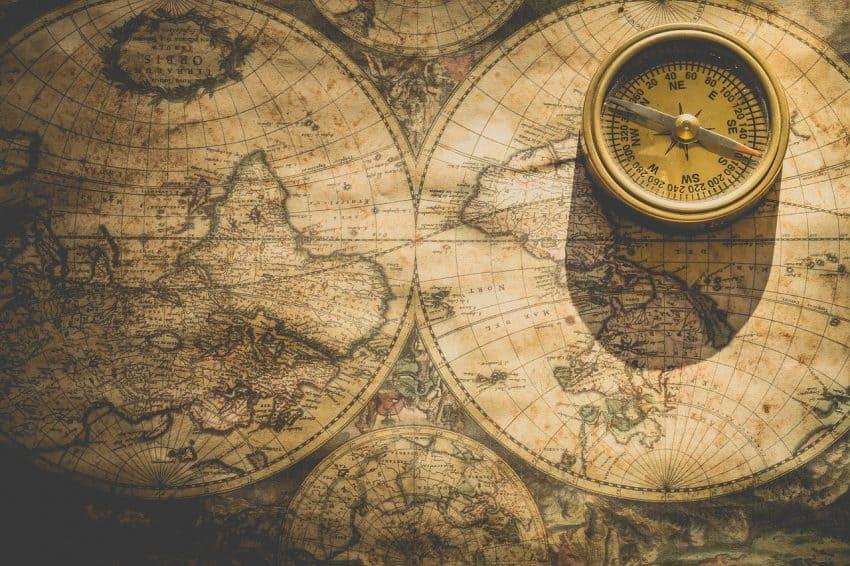 Imagem mostra uma bússola em cima de um grande mapa com ângulos diferentes do planeta Terra.