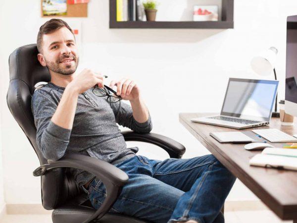 Imagem mostra homem trabalhando com cadeira de escritório presidente.