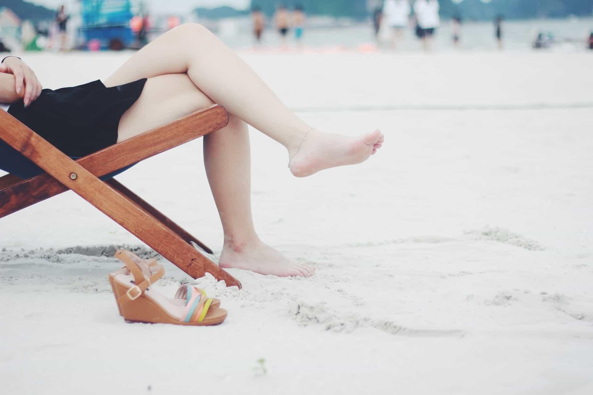 Imagem mostra pessoa sentada em uma cadeira de praia e um par de sandálias ao lado.