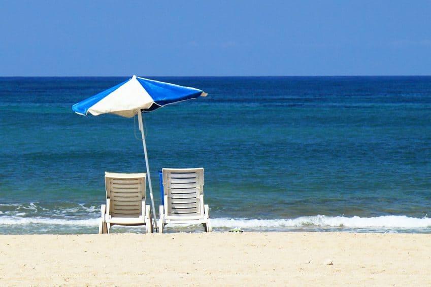 Imagem mostra duas cadeiras de praia e um guarda-sol em frente ao mar.