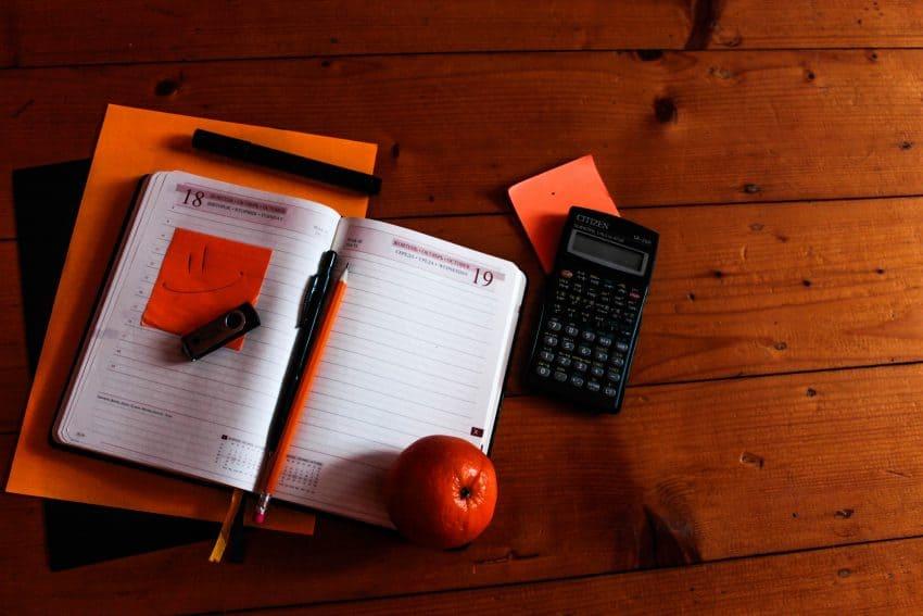 Imagem mostra uma calculadora científica ao lado de uma agenda aberta, que possui uma maçã em cima de uma de suas páginas.