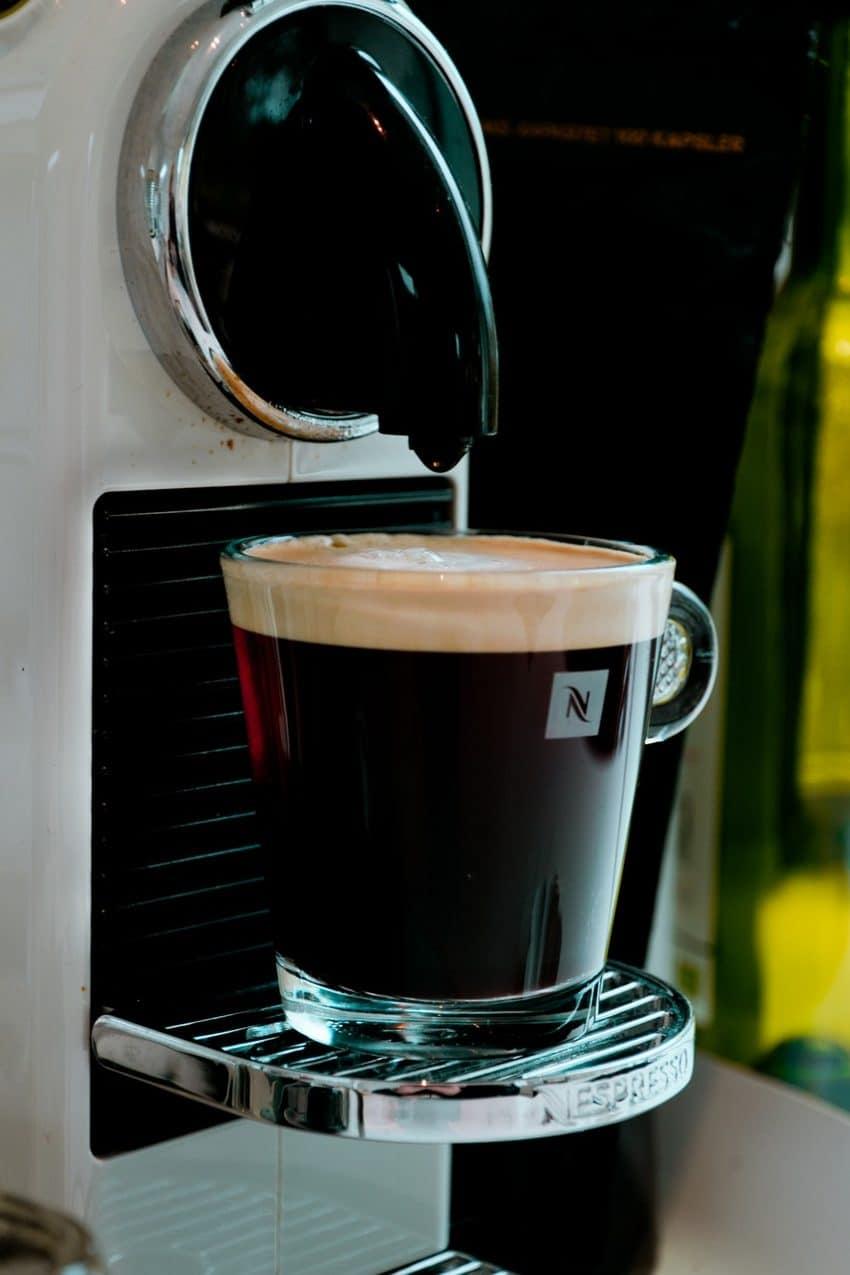 Imagem mostra cafeteira em cápsula nespresso branca com xícara de café.
