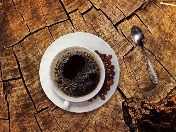 Imagem mostra xícara de café vista de cima com grãos de café ao lado.