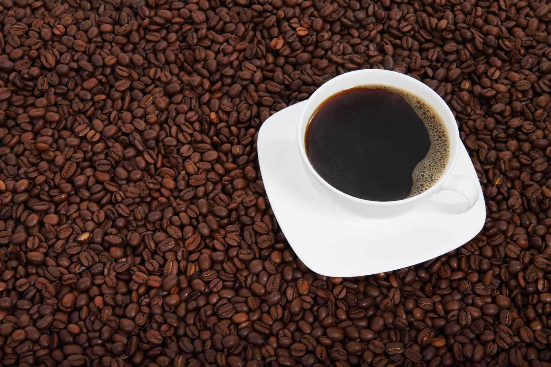 Imagem mostra xícara de café com café em grãos em volta.