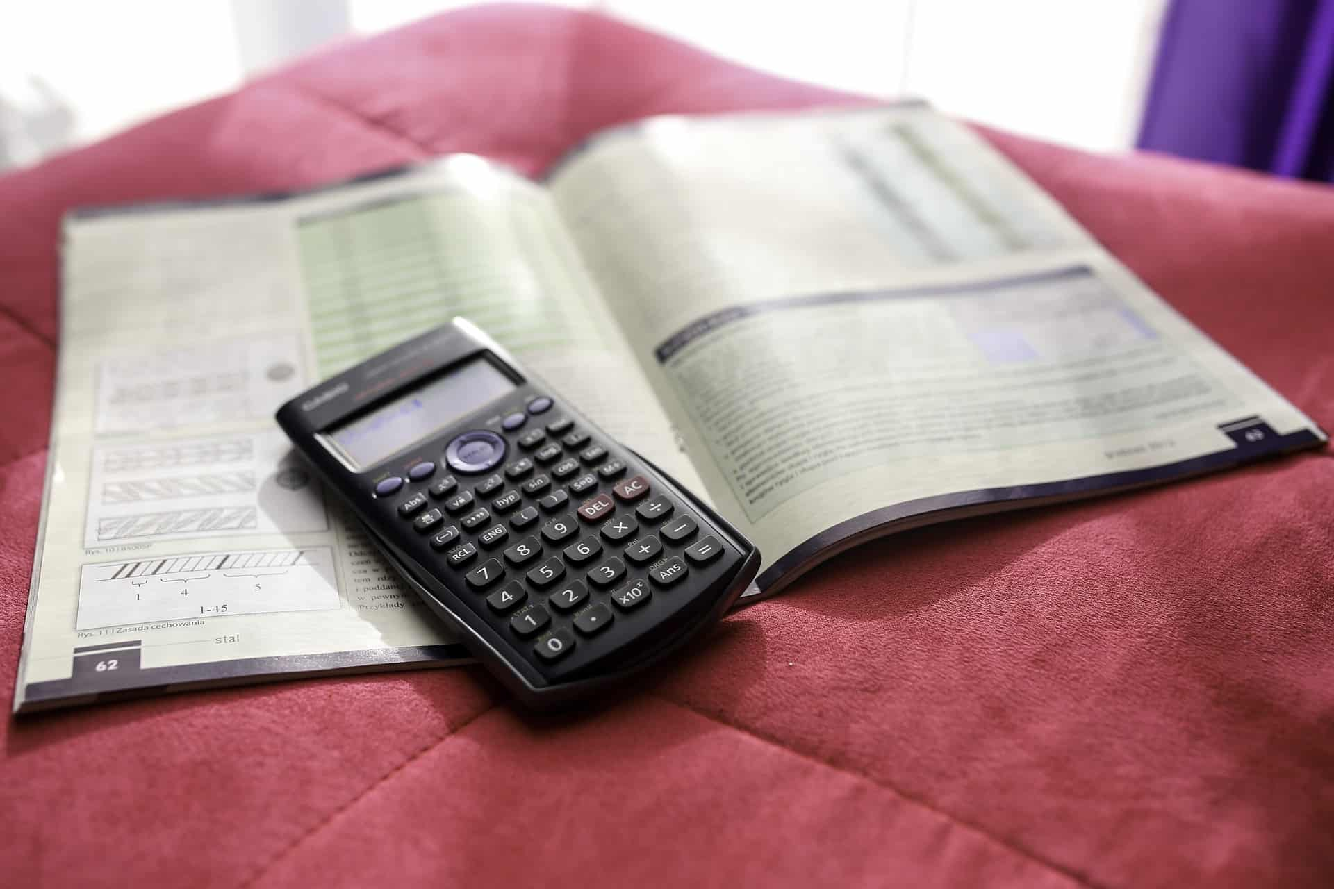 Imagem mostra uma calculadora científica em cima de livro.