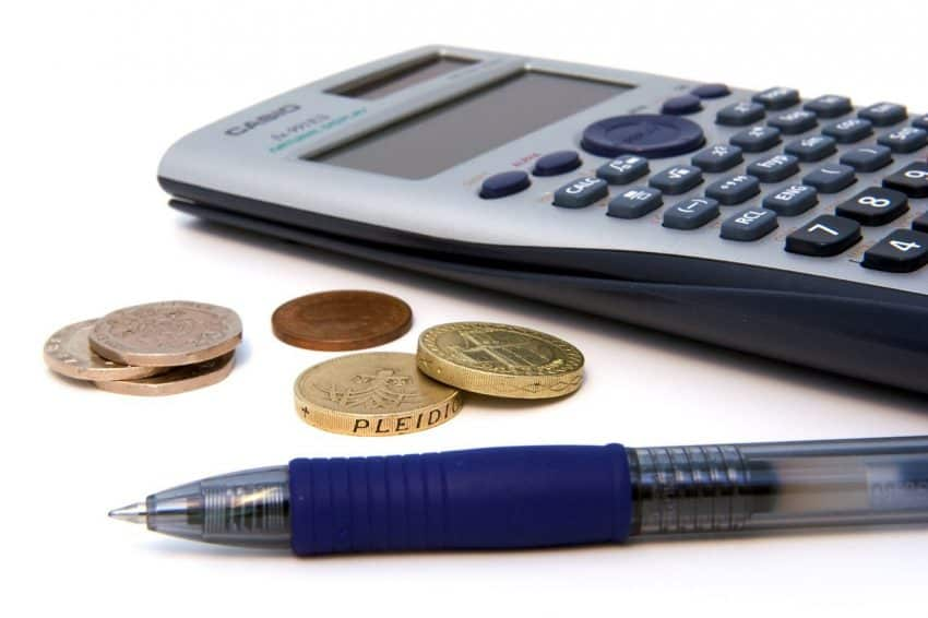 Imagem mostra uma caneta ao lado de algumas moedas e de uma calculadora financeira.