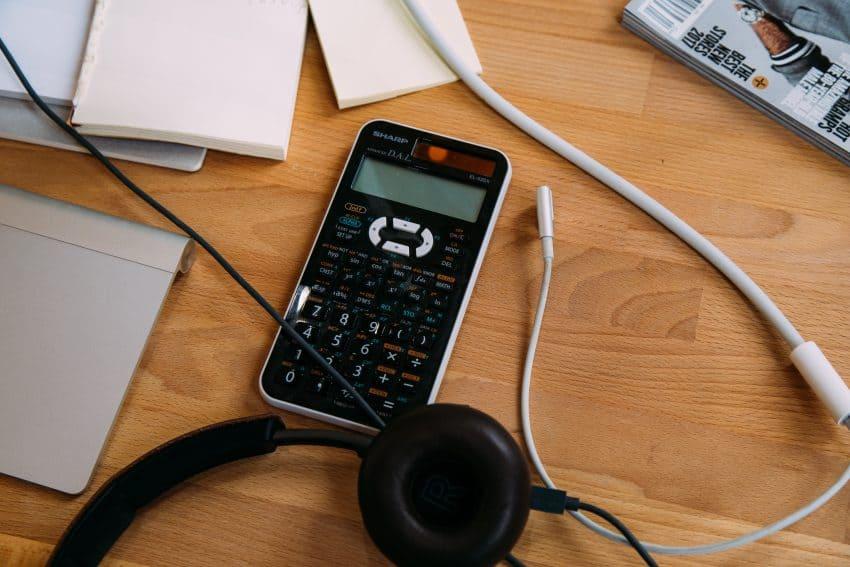 Imagem mostra uma calculadora científica em cima de uma mesa, ao lado de um fone de ouvido.