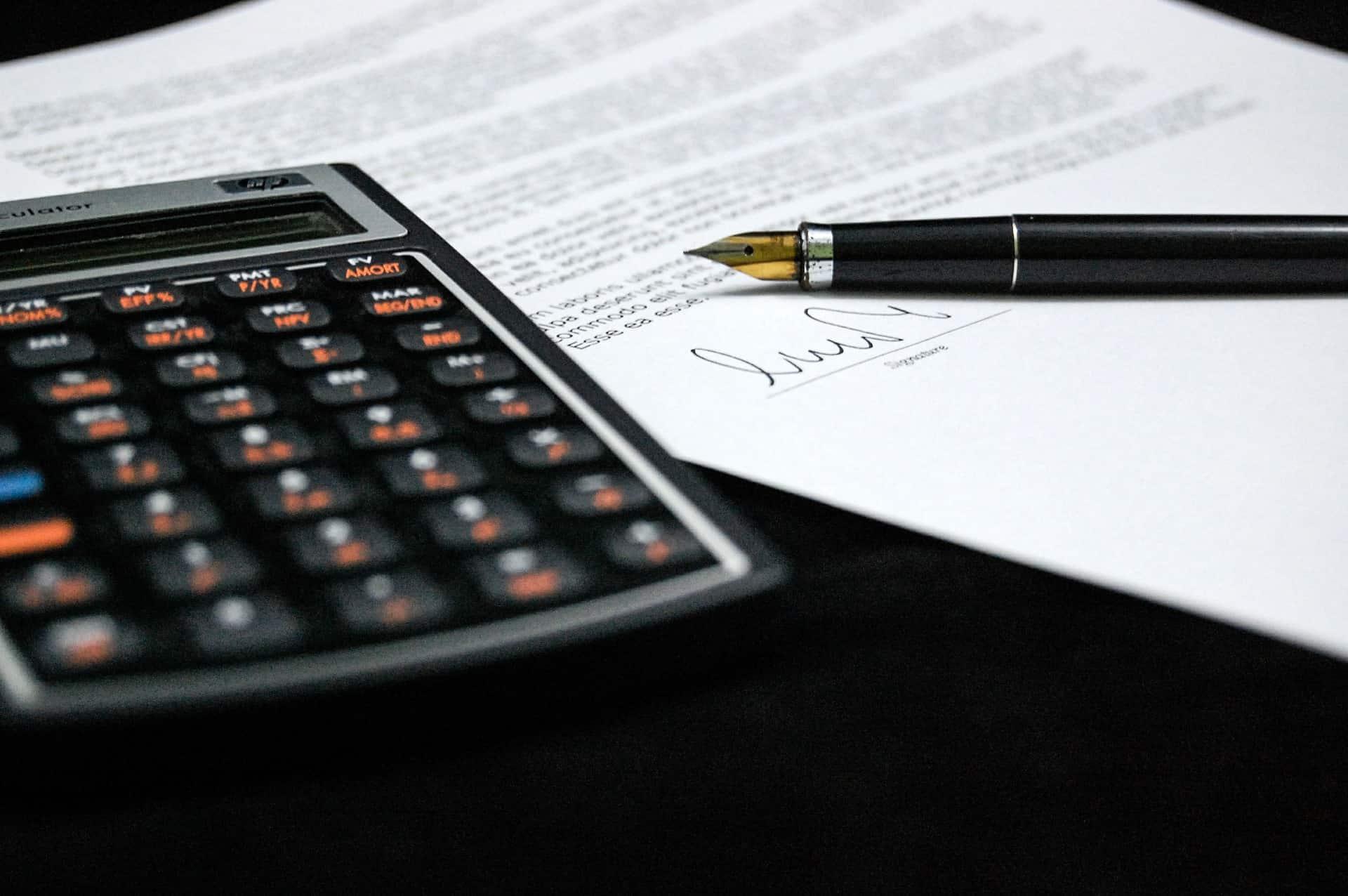 Imagem mostra uma calculadora financeira ao lado de um documento e uma caneta.