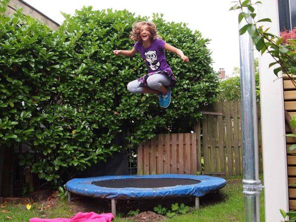 Imagem mostra menina saltando na cama elástica em um jardim.