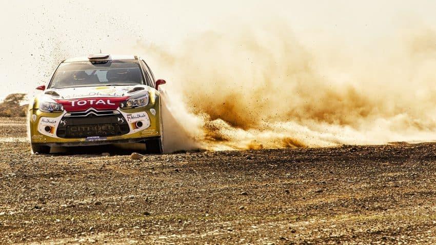 Imagem mostra carro de corrida derrapando em terreno arenoso, levantando poeira.