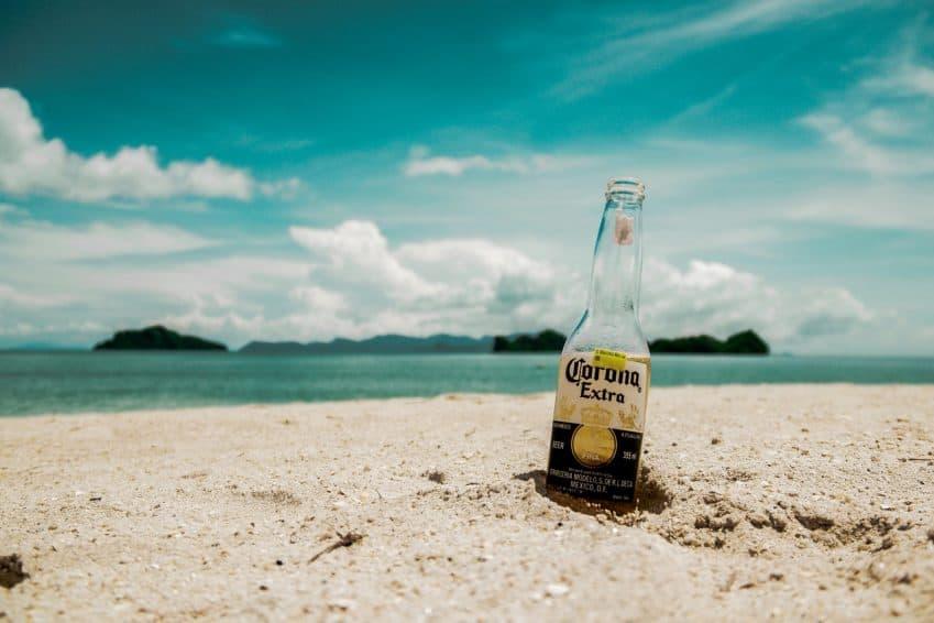 Imagem mostra cerveja em pé na areia da praia.