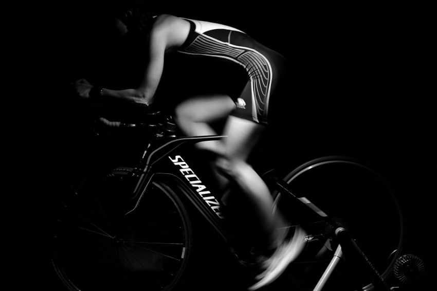 Imagem mostra ciclista pedalando em alta velocidade ao centro, sob uma bike preta e fundo preto.