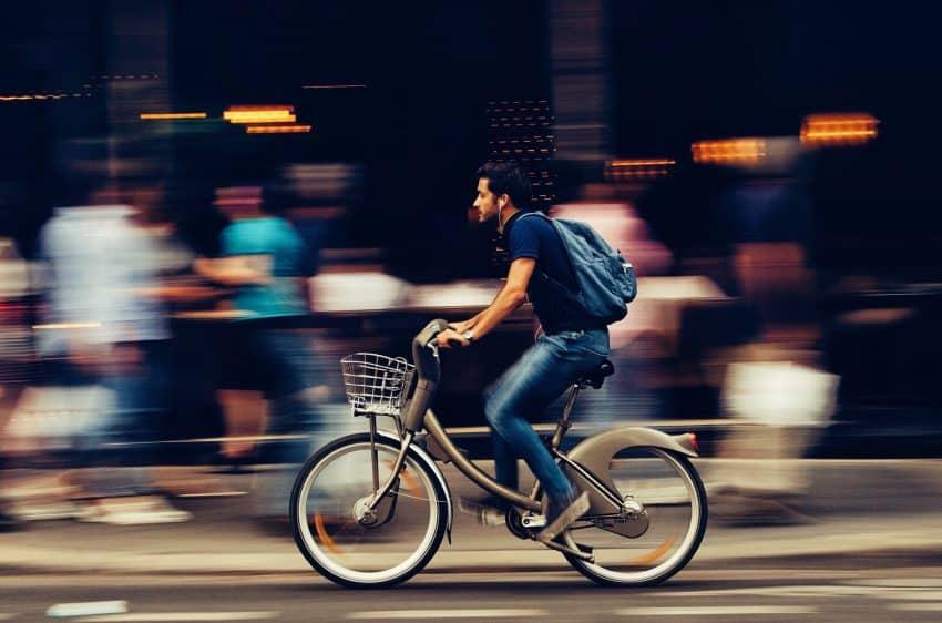 Em primeiro plano ciclista pedalando em alta velocidade na rua, com pedestres desfocados em segundo plano.