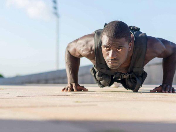 Imagem mostra homem fazendo flexões vestindo um colete de peso.