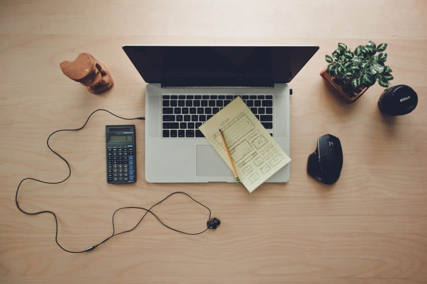 Imagem mostra um computador com um caderno e um lápis em cima do seu teclado, e uma calculadora científica ao lado.