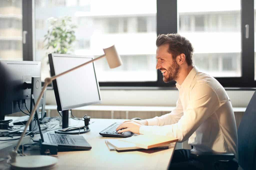 homem sorrindo em frente a um computador