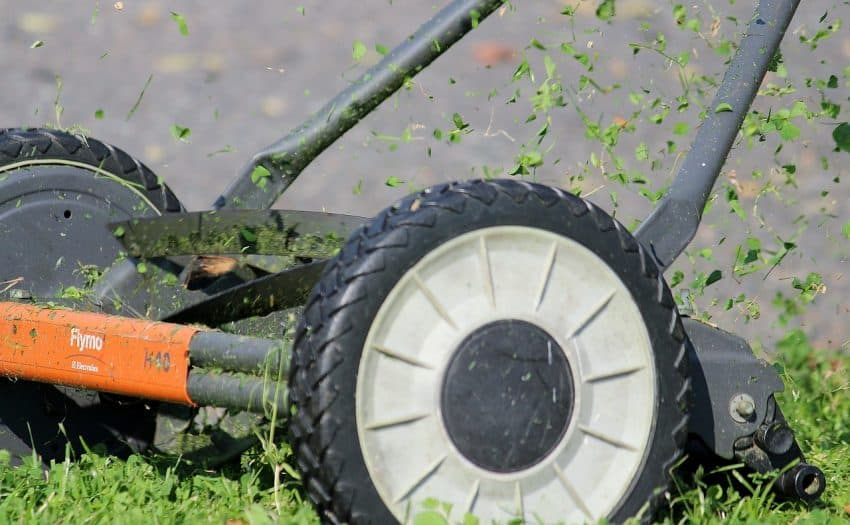 Imagem mostra cortador de grama manual com lâminas rotativas cortando um gramado.