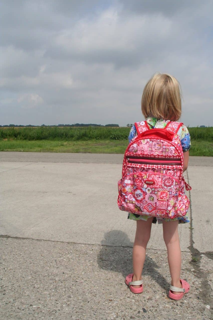 Imagem mostra menina com mochila nas costas aguardando ônibus.