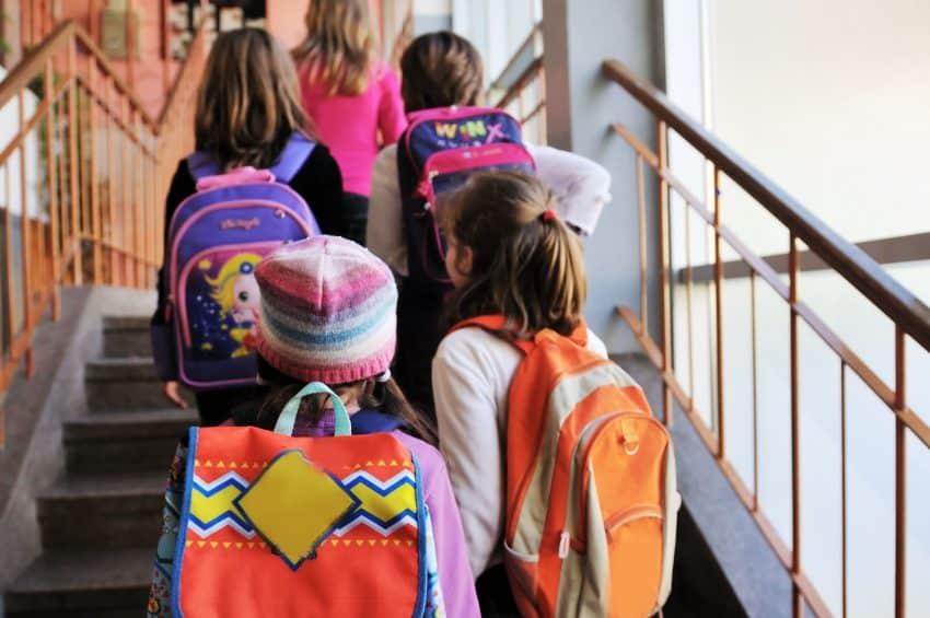 Imagem mostra crianças subindo a escada da escola com mochila infantil nas costas.