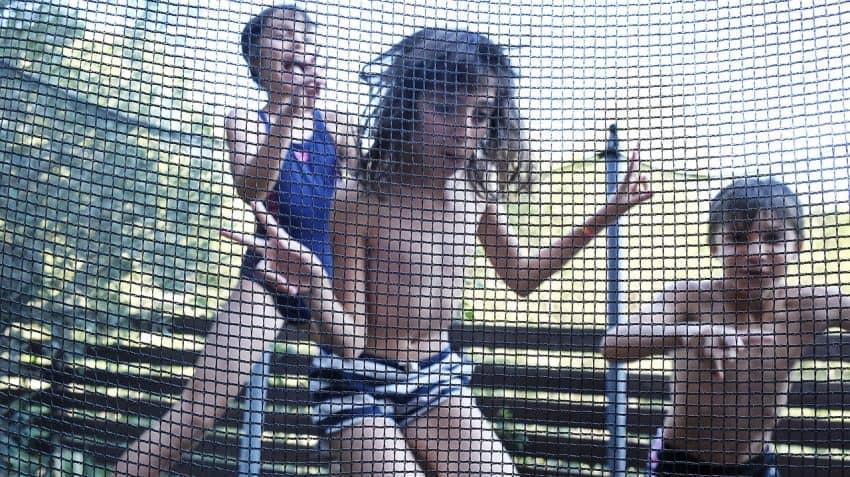 Imagem mostra três crianças brincando em uma cama elástica, vistas através da tela de proteção.