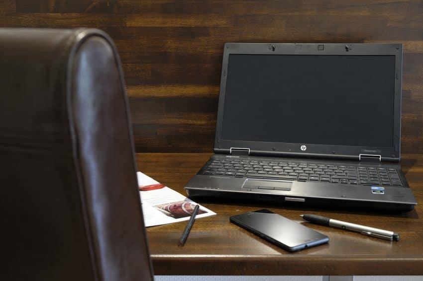 Imagem mostra cadeira de escritório perto da mesa com notebook, celular e caneta.