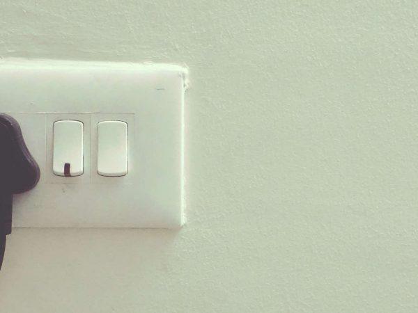 Imagem mostra cabo conectado à tomada na parede.