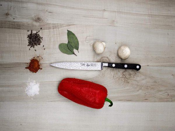 Imagem mostra faca disposta sobre tábua de madeira, com punhados de temperos coloridos, pimentão e cogumelos frescos.