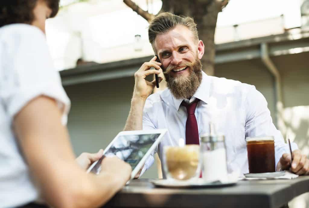 homem falando no celular em uma mesa de café