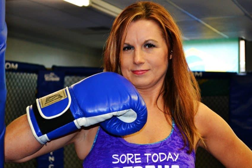 mulher boxeador com luva de boxe azul perto do rosto