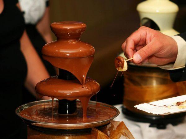 Imagem de uma uma fonte de chocolate em uma mesa de buffet com o close da mão de um homem melando um pedaço de banana no chocolate.