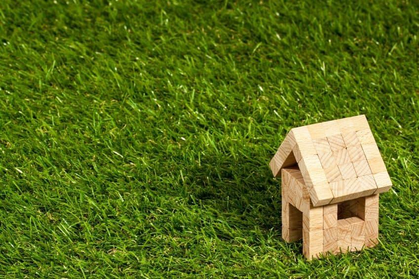 Imagem mostra gramado em close com pequena casinha de madeira.