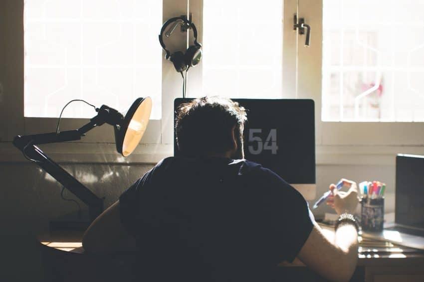Imagem mostra homem de costas sentado em frente a um computador.