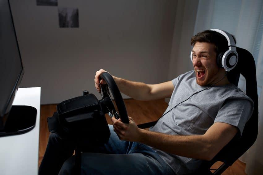 Imagem mostra homem feliz jogando com um volante para PC usando fone de ouvido.