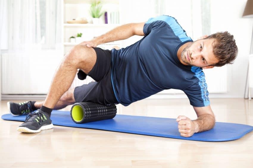 homem fazendo automassagem com rolo de massagem em tapete de exercício azul