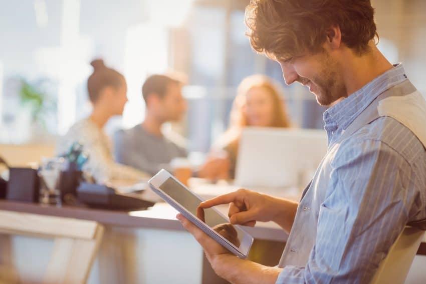 homem sorrindo sentado em local público usando um tablet branco,
