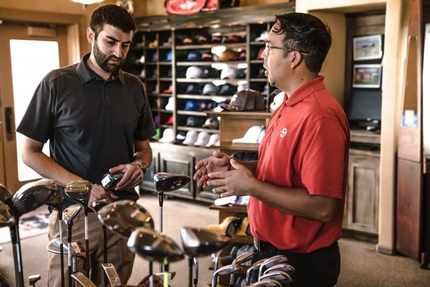 Imagem mostra vendedor de loja de artigos esportivos conversando com cliente.