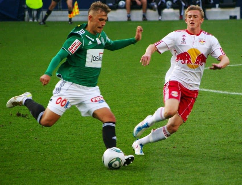 Imagem mostra dois homens jogando futebol de campo. um deles está prestes a chutar a bola.