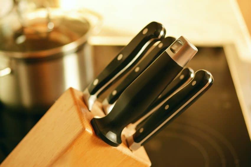 Imagem mostra um jogo de facas inseridas em um suporte de madeira.