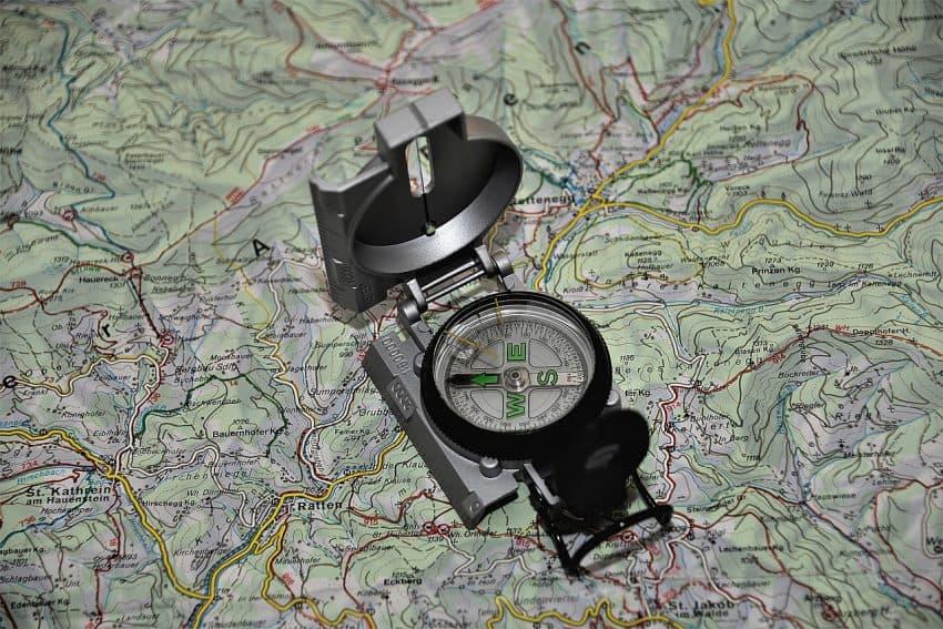 Imagem mostra uma bússola aberta em cima de um mapa das vias de uma cidade.
