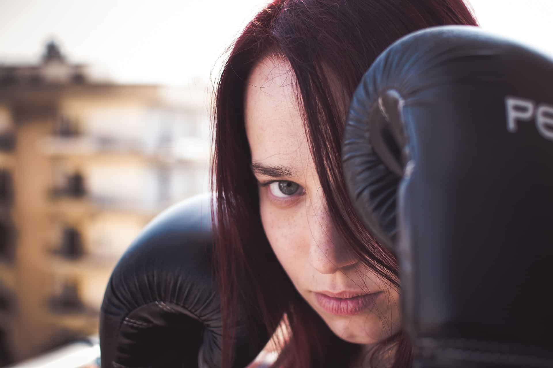 Imagem mostra mulher com luva de boxe preta cobrindo seu olho esquerdo.