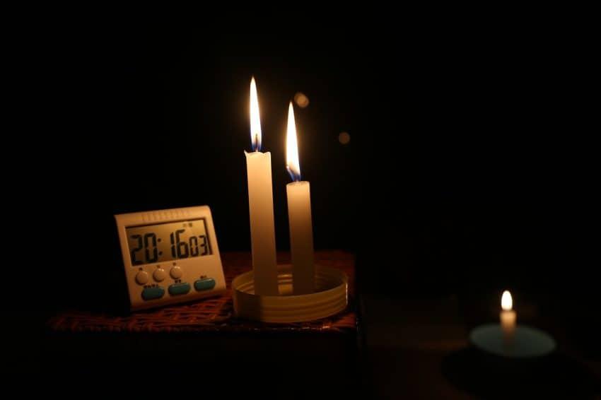 Imagem mostra quarto escuro, com vela acesa e despertador ao lado.