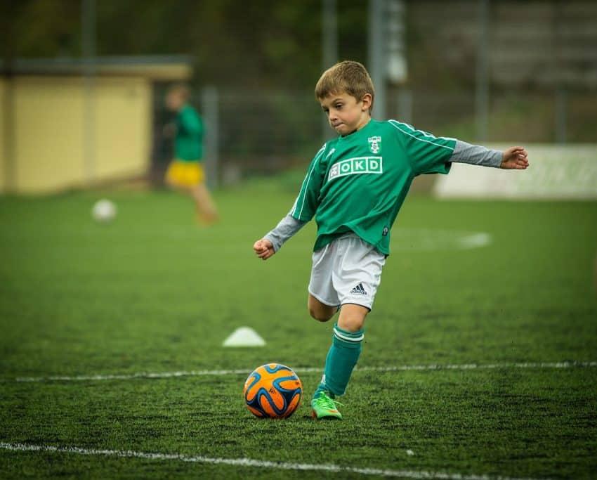 Jovem jogador de uniforme verde prepara-se para chutar uma bola, em tamanho menor, ideal para a sua idade.